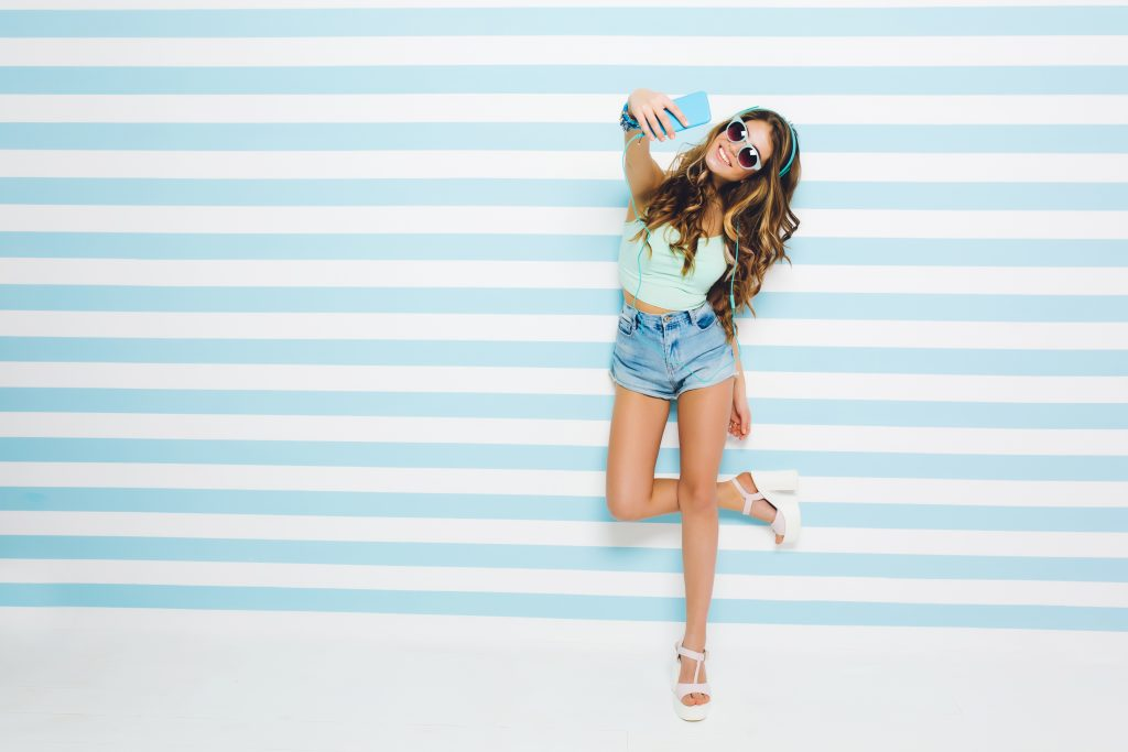 Long Haired Tanned Girl Wearing Denim Shorts And Heeled Sandals Standing On One Leg And Making Selfie With Smile. Full Length Portrait Of Young Woman In Sunglasses Posing On Striped Background..